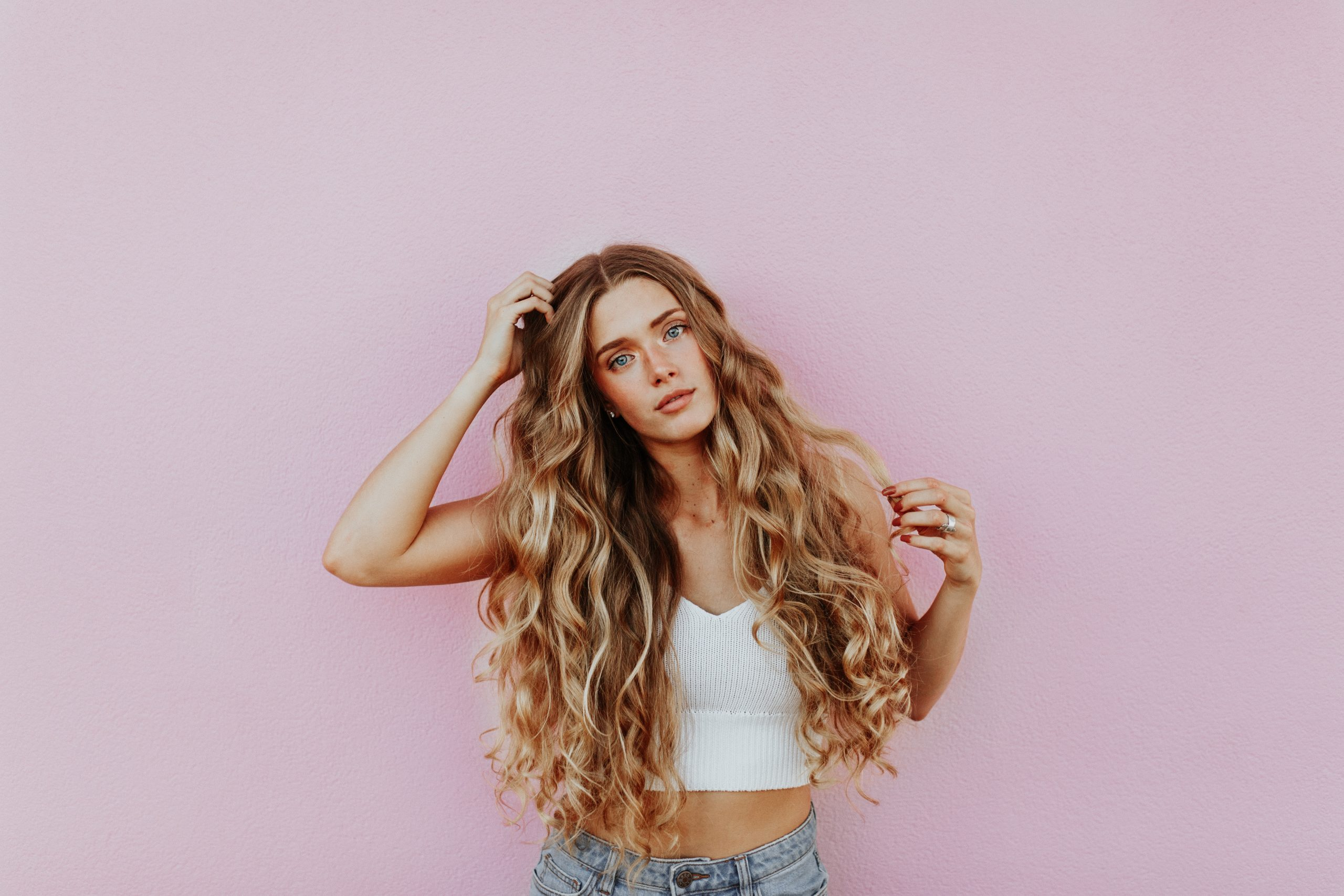 A blonde model posing for a shot against a pink background