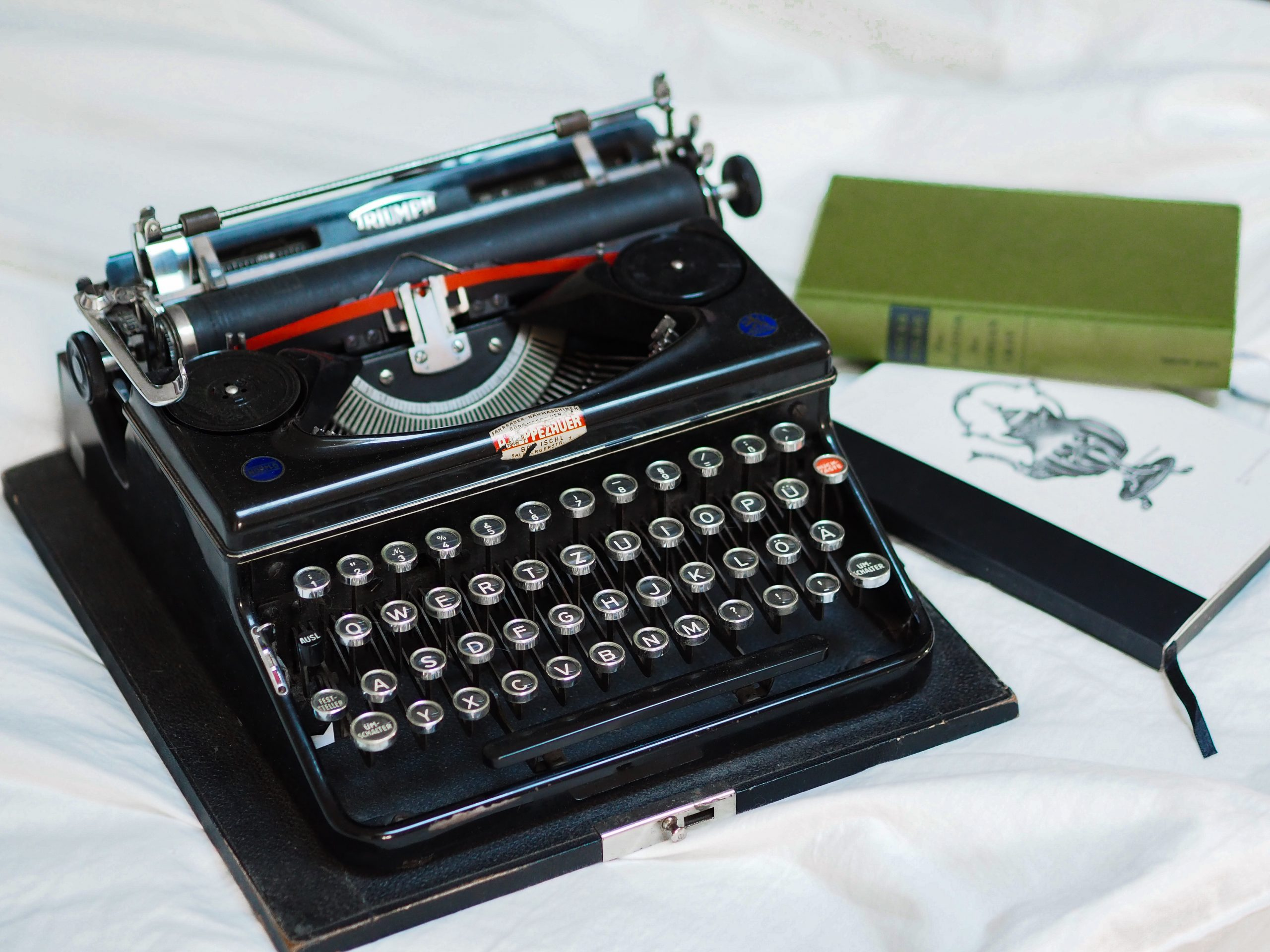 A black typewriter on a table with some books